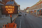 FILE - In this Dec. 2, 2020, file photo, a flashing sign on Court Street in Athens, Ohio, reports the number of active COVID-19 cases in the community. States faced a deadline on Friday, Dec. 4, 2020, to place orders for the coronavirus vaccine as many reported record infections, hospitalizations and deaths, while hospitals were pushed to the breaking point — with the worstfearedyet to come. (Doral Chenoweth/The Columbus Dispatch via AP, File)