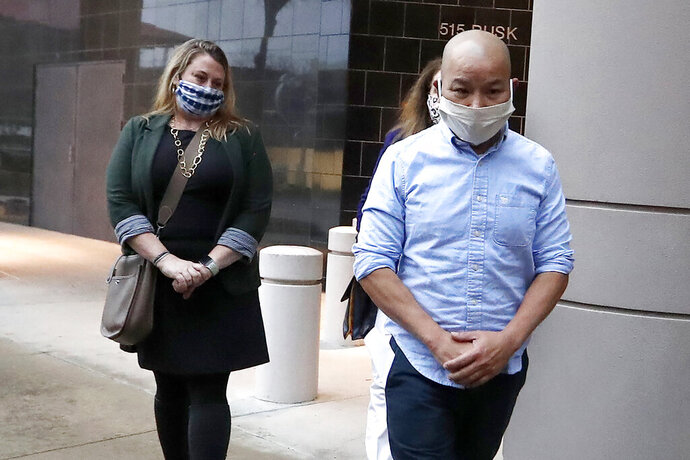 In this Jan. 21, 2021, photo former Houston Police Officer Tam Pham walks out of the Federal Courthouse downtown in Houston after he appeared in court following his arrest Wednesday on federal charges tied to Capitol violence. Police departments across the country are reviewing the behavior of dozens of officers who were in Washington on the day of a riot at the U.S. Capitol. (Karen Warren/Houston Chronicle via AP)