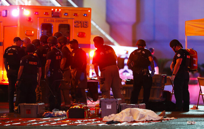 FILE - In this Oct. 1, 2017, file photo, a body is covered with a sheet after a mass shooting in which dozens were killed at a music festival on the Las Vegas Strip in Las Vegas. Witness accounts of gunfire, chaos, blood, heartbreak and survival emerged Wednesday, May 16, 2018, in police reports made public seven months after the shooting that became the deadliest event of its kind in modern U.S. history.  (Steve Marcus /Las Vegas Sun via AP, File)