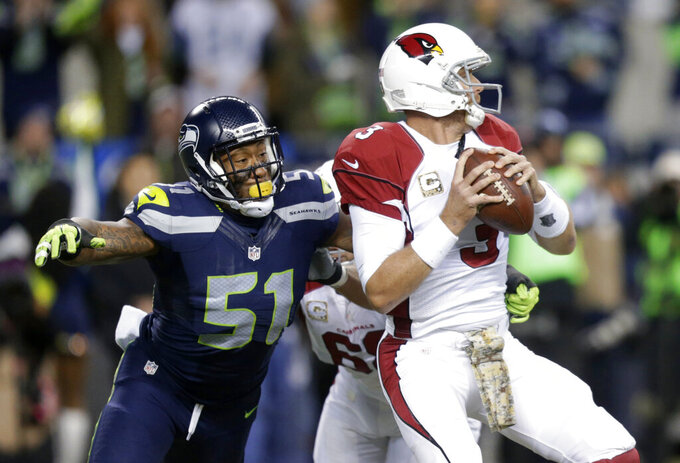 FILE - In this Nov. 15, 2015, file photo, Seattle Seahawks outside linebacker Bruce Irvin (51) pressures Arizona Cardinals quarterback Carson Palmer during the first half of an NFL football game in Seattle. Irvin is thrilled to be back where his NFL journey started. Irvin jumped at the chance to return to Seattle this offseason, but his reunion with the Seahawks comes with the expectation he can help a lackluster pass rush. (AP Photo/Stephen Brashear, File)
