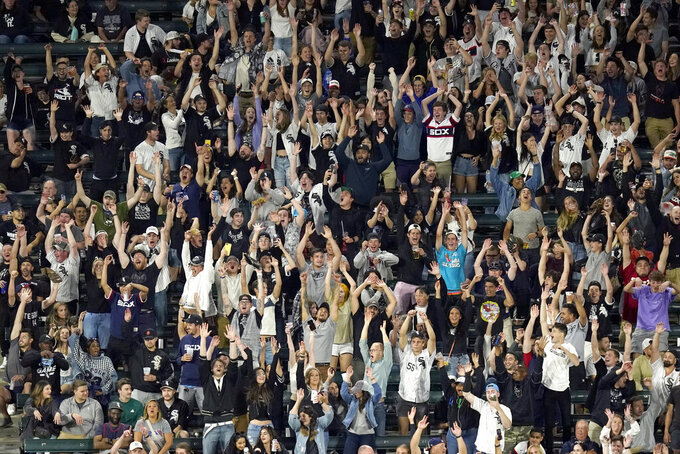 Fans do the wave in the left field bleachers during the eighth inning of a baseball game between the Chicago White Sox and the Tampa Bay Rays on Tuesday, June 15, 2021, in Chicago. Guaranteed Rate Field is scheduled to return to full capacity June 25. (AP Photo/Charles Rex Arbogast)