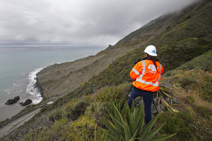 File - In this May 25, 2017, file photo, Cal Trans public affairs officer Jessica Biro photographs the southern end of the Mud Creek slide as it covers Highway One in southern Monterey County on the coast in Big Sur, Calif. The California Department of Transportation plans to temporarily close landslide-plagued Highway 1 on the southern Big Sur coast when there are forecasts of significant rains this winter. The Monterey Herald reports Caltrans will notify the public 48 hours before any potential closures, which would take place at Mud Creek or Paul's Slide. (Vern Fisher/The Monterey County Herald via AP, File)