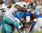 Carolina Panthers' Cam Newton, right, is sacked by Miami Dolphins' Robert Quinn, left, in the first half of a preseason NFL football game in Charlotte, N.C., Friday, Aug. 17, 2018. (AP Photo/Mike McCarn)