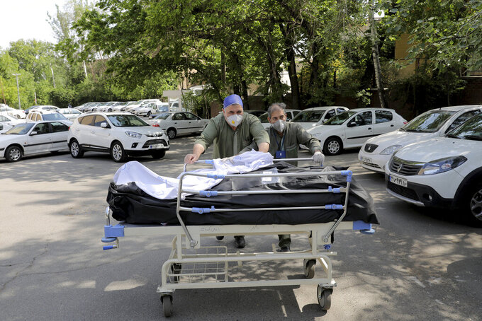 Hospital workers move two bodies of patients who died from COVID-19, at the yard of the Shohadaye Tajrish Hospital in Tehran, Iran, Sunday, April 18, 2021. After facing criticism for downplaying the virus last year, authorities have put partial lockdowns and other measures in place to try and slow the coronavirus' spread, as Iran faces what looks like its worst wave of the coronavirus pandemic yet. (AP Photo/Ebrahim Noroozi)