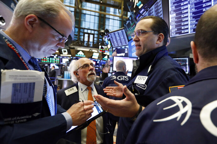 FILE- In this Feb. 15, 2019, file photo specialist Anthony Matesic, right, works with traders on the floor of the New York Stock Exchange. The U.S. stock market opens at 9:30 a.m. EST on Wednesday, Feb. 20. (AP Photo/Richard Drew, File)