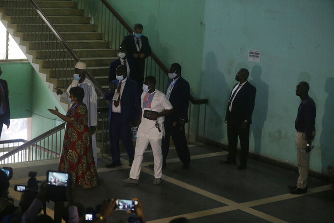 Ambassadors and foreign representations, leave after a meeting with Military junta led by Col. Mamady Doumbouya, at the people's palace in Conakry, Guinea Wednesday, Sept. 15, 2021. Guinea's junta is expected to face more pressure to set a timeframe for new elections Tuesday as the military rulers open a four-day series of meetings about the West African nation's future following the president's overthrow in a coup just over a week ago. (AP Photo/Sunday Alamba)