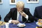 Britain's Prime Minister Boris Johnson enjoys a cream tea during a photocall while touring 'Rodda's Clotted Cream', in Redruth, England, Wednesday, Nov. 27, 2019 (Dan Kitwood/Pool Photo via AP)