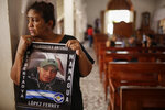 Martha Lorena Alvarado, mother of jailed anti-government demonstrator Melkkisedex Antonio Lopez, holds a sign with an image of her son at the San Miguel Arcangel Church in Masaya, Nicaragua, Thursday, Nov. 14, 2019. Alvarado has joined a hunger strike to demand the freedom of their relatives, jailed for protesting against the government of President Daniel Ortega. (AP Photo/Alfredo Zuniga)