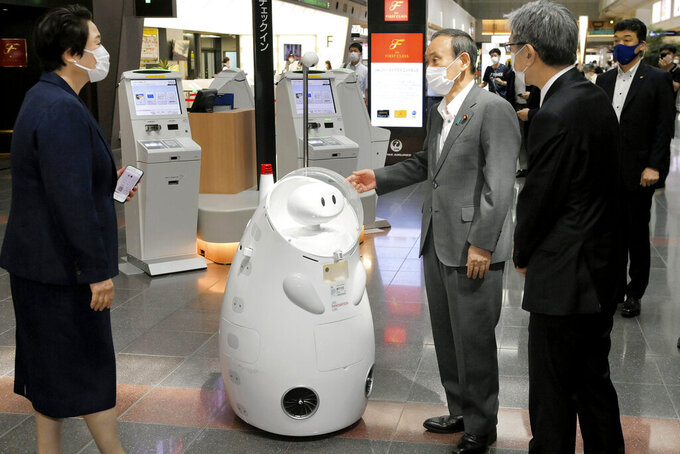 Japanese Prime Minister Yoshihide Suga, center, stands by a remotely-controlled guide robot at Haneda international airport in Tokyo, Monday, June 28, 2021. Suga inspected antigen testing for arrivals and vowed to ensure appropriate border controls as growing numbers of Olympic and Paralympic participants enter Japan ahead of the July 23 opening of the games (Kyodo News via AP)