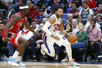 Detroit Pistons guard Derrick Rose (25) drives by New Orleans Pelicans guard Jrue Holiday (11) in the first half of an NBA basketball game in New Orleans, Monday, Dec. 9, 2019. (AP Photo/Brett Duke)