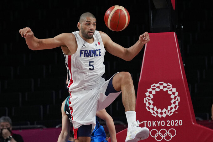 France's Nicolas Batum (5) blocks a last second scoring attempt by Slovenia's Klemen Prepelic during a men's basketball semifinal round game at the 2020 Summer Olympics, Thursday, Aug. 5, 2021, in Saitama, Japan. (AP Photo/Eric Gay)