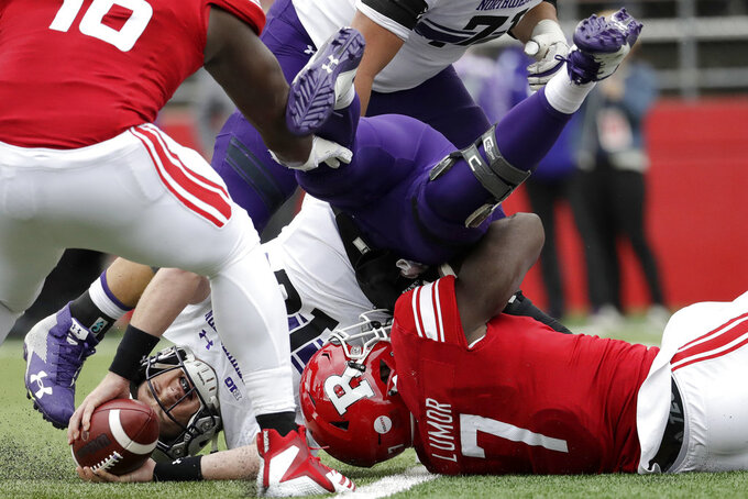 Northwestern quarterback Clayton Thorson, left, is sacked by Rutgers defensive lineman Elorm Lumor during the first half of an NCAA college football game, Saturday, Oct. 20, 2018, in Piscataway, N.J. (AP Photo/Julio Cortez)