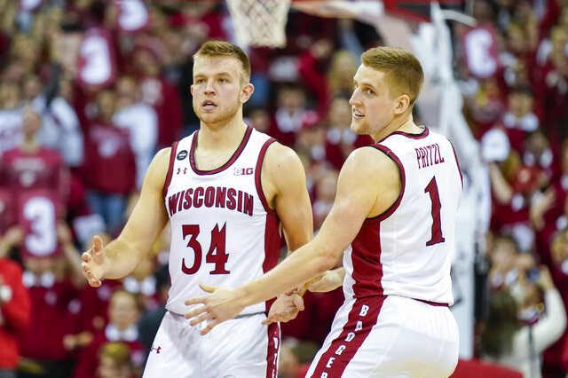 Wisconsin's Brad Davison (34) congratulates Brevin Pritzl (1) after Pritzl hit a three-point basket against Ohio State during the second half of an NCAA college basketball game Sunday, Feb. 9, 2020, in Madison, Wis. (AP Photo/Andy Manis)