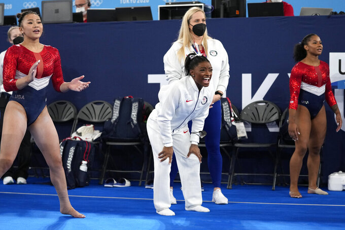 Gymnasts from the United States, Simone Biles, centre, Jordan Chiles , right, and Sunisa Lee cheer the performance of teammate Grace McCallum performs on the floor during the artistic gymnastics women's final at the 2020 Summer Olympics, Tuesday, July 27, 2021, in Tokyo. (AP Photo/Ashley Landis)