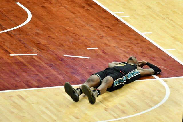 Memphis Grizzlies guard Ja Morant (12) lies on the court in the second half of an NBA basketball game against the Phoenix Suns, Monday, Jan. 18, 2021, in Memphis, Tenn. (AP Photo/Brandon Dill)