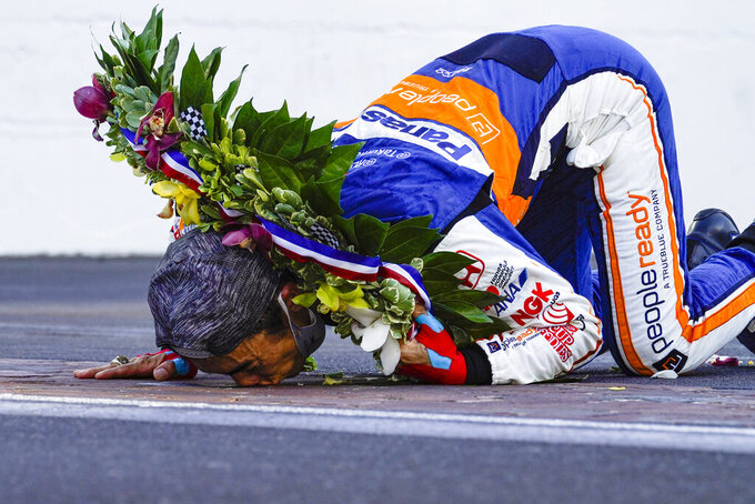 Takuma Sato, of Japan, kisses the yard of bricks on the start/finish line after winning the Indianapolis 500 auto race at Indianapolis Motor Speedway in Indianapolis, Sunday, Aug. 23, 2020. (AP Photo/Michael Conroy)
