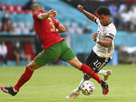 Portugal's Pepe, left, tries to tackle Germany's Serge Gnabry during the Euro 2020 soccer championship group F match between Portugal and Germany at the football arena stadium in Munich, Saturday, June 19, 2021. (Christof Stache/Pool via AP)