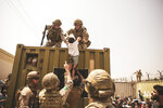 In this image provided by the U.S. Marine Corps, British and Turkish coalition forces, along with U.S. Marines, assist a child during an evacuation at Hamid Karzai International Airport in Kabul, Afghanistan, Friday, Aug. 20, 2021. (Staff Sgt. Victor Mancilla/U.S. Marine Corps via AP)