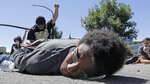 A man lies in the street with his hands behind his back while others demonstrate during a march in Salt Lake City, Friday, June 19, 2020, in Salt Lake City, to mark Juneteenth, the holiday celebrating the day in 1865 that enslaved black people in Galveston, Texas, learned they had been freed from bondage, more than two years after the Emancipation Proclamation. (AP Photo/Rick Bowmer)