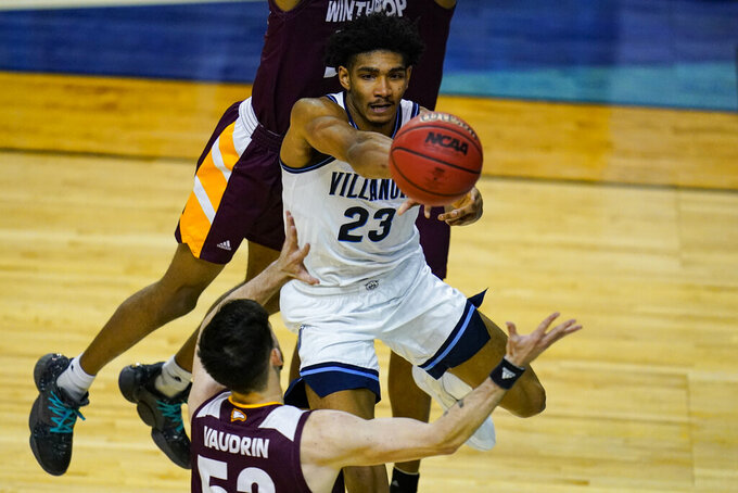 Villanova forward Jermaine Samuels (23) makes a pass over Winthrop guard Chandler Vaudrin (52) in the first half of a first round game in the NCAA men's college basketball tournament at Farmers Coliseum in Indianapolis, Friday, March 19, 2021. (AP Photo/Michael Conroy)