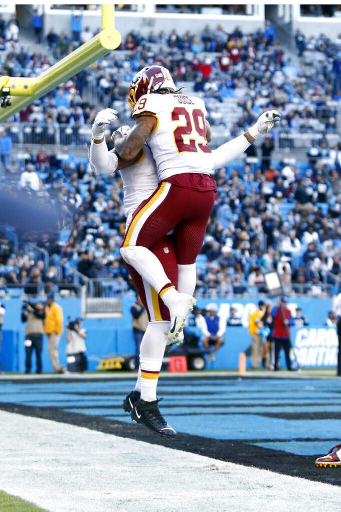 Washington Redskins running back Derrius Guice (29) and offensive guard Ereck Flowers celebrate Guice's touchdown against the Carolina Panthers during the second half of an NFL football game in Charlotte, N.C., Sunday, Dec. 1, 2019. (AP Photo/Brian Blanco)