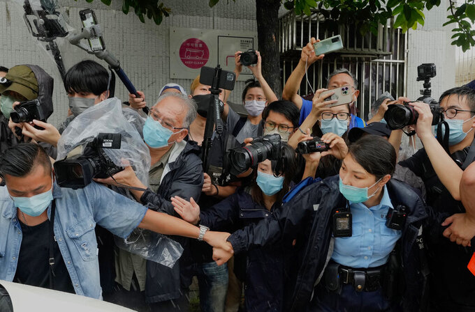Photographers surround a van which was carrying Agnes Chow, a prominent pro-democracy activist sentenced to jail last year for taking part in unauthorized assemblies during the 2019 protest movement, after her release Saturday, June 12, 2021, in Hong Kong. (AP Photo/Vincent Yu)