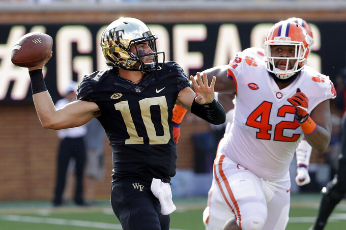 Wake Forest's Sam Hartman (10) looks to pass under pressure from Clemson's Christian Wilkins (42) during the first half of an NCAA college football game in Charlotte, N.C., Saturday, Oct. 6, 2018. (AP Photo/Chuck Burton)