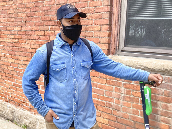"""Christoph Cunningham, of Detroit, said he's fully vaccinated but wore a mask Friday, May 14, 2021, on his way to lunch at a bar. He said he agrees with the new federal and state mask policies. """"I have confidence in the science behind it all,"""" said Cunningham, who works in the culinary field. """"I'll eventually take my mask off more and more. I might take it off to make other people comfortable. ... If you don't feel comfortable not wearing a mask, I think you should be able to keep it on. Don't beat anyone down."""" (AP Photo/Ed White)"""