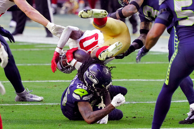 San Francisco 49ers running back Jeff Wilson is tackled y Seattle Seahawks cornerback Shaquill Griffin (26) during the first half of an NFL football game, Sunday, Jan. 3, 2021, in Glendale, Ariz. (AP Photo/Rick Scuteri)