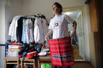 In this picture taken Tuesday, May 21, 2019, Valentina Radu shows traditional clothing items she produces in Luncavita, Romania. Radu also worked in Italy, but when her husband lost his job there, they struggled to pay the rent and decided to come home where they used European Union funds to buy a small farm and she further opened a tailor's shop. (AP Photo/Vadim Ghirda)