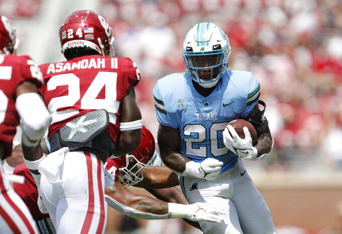 Tulane running back Cameron Carroll (20) works to escape a tackle by Oklahoma linebacker Brian Asamoah (24) during an NCAA college football game Saturday, Sept. 4, 2021, in Norman, Okla. (AP Photo/Alonzo Adams)