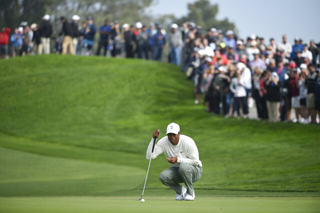 Tiger Woods lines up a putt on the second hole of the South Course at Torrey Pines Golf Course during the second round of the Farmers Insurance golf tournament Friday Jan. 24, 2020, in San Diego. (AP Photo/Denis Poroy)