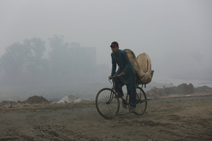 A man rides his laden bike through smog, in Lahore, Pakistan, Friday, Nov. 22, 2019. Tens of thousands of people in Pakistan's eastern city are at risk of respiratory disease because of poor air quality related to thick smog hanging over the region, an international rights group said Friday. (AP Photo/K.M. Chaudary)
