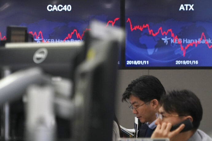 A currency trader talks on the phone at the foreign exchange dealing room in Seoul, South Korea, Wednesday, Jan. 15, 2020. Asian shares have retreated as conflicting reports raised concerns over the likely outcome of a trade deal to be signed by the U.S. and China. (AP Photo/Lee Jin-man)