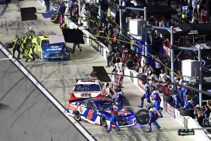 Kyle Larson (5), Ryan Blaney, center, and Matt DiBenedetto, back, come in for a pit stop in the NASCAR Cup Series auto race at Daytona International Speedway, Saturday, Aug. 28, 2021, in Daytona Beach, Fla. (AP Photo/David Graham)
