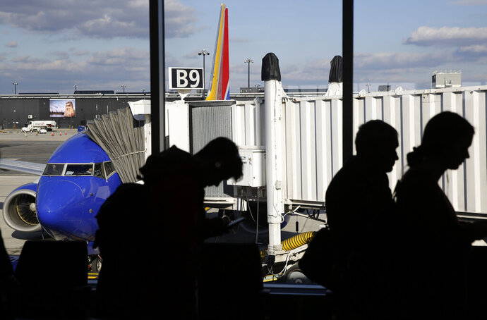 FILE - In this Nov. 20, 2018, file photo travelers wait in line to board a flight at Baltimore-Washington International Thurgood Marshall Airport in Linthicum, Md. Airlines expect record crowds over the week-long Labor Day period, continuing a rise in travel that has boosted the airlines' profits all year. (AP Photo/Patrick Semansky, File)