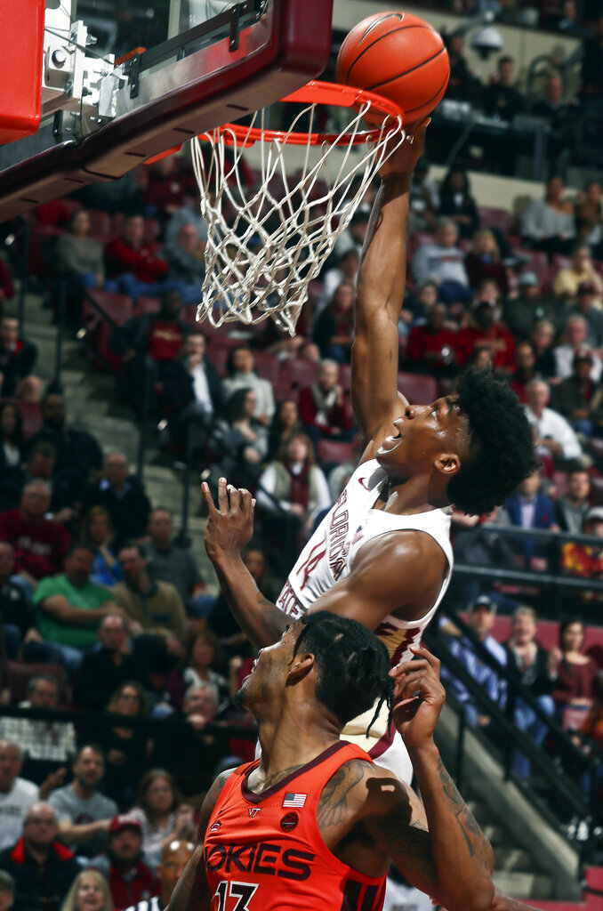 Florida State guard Terance Mann (14) makes a layup as Virginia Tech guard Ahmed Hill (13) looks on in the second half of an NCAA college basketball game in Tallahassee, Fla., Tuesday, March 5, 2019. Florida State won 73-64 in overtime. (AP Photo/Phil Sears)