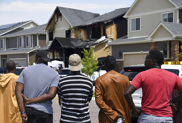 FILE - In this Aug. 5, 2020, file photo, people look at a house where five people were found dead after a fire in Denver. Three teenagers have been arrested in connection with the fire that killed five recent immigrants, including two children, from the West African nation of Senegal, police said Wednesday, Jan. 27, 2021. (AP Photo/Thomas Peipert, File)
