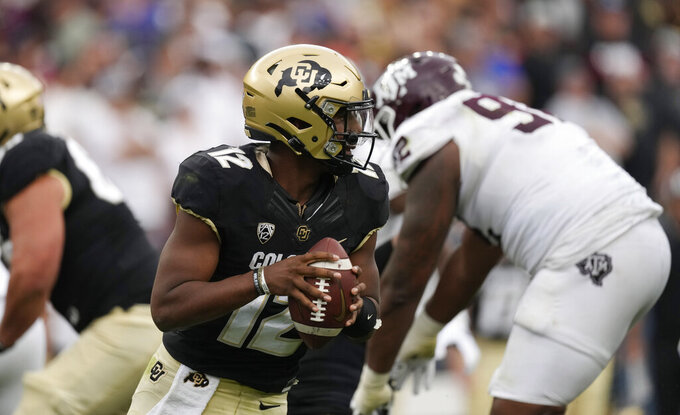 Colorado quarterback Brendon Lewis evades Texas A&M defenders in the second half of an NCAA college football game Saturday, Sept. 11, 2021, in Denver. Texas A&M won 10-7. (AP Photo/David Zalubowski)