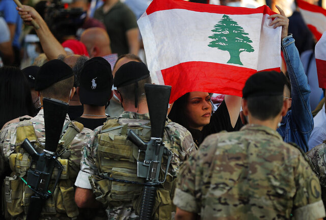 An anti-government protester holds a national flag, as she passes in front of Lebanese army soldiers during a protest against rising prices and worsening economic and financial conditions, in Zalka, north of Beirut, Lebanon, Monday, Oct. 5, 2020. Lebanon is passing through its worst economic and financial crisis in decades made worse by the coronavirus pandemic. (AP Photo/Hussein Malla)