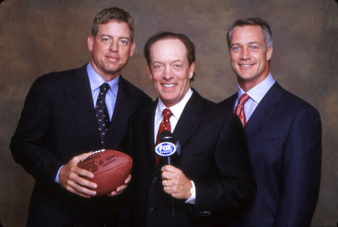 In this 2001 photo provided by Fox Sports, Troy Aikman, Dick Stockton and Daryl Johnston, from left, pose for a photo, location not known. Stockton has done his final game on network television after a 55-year career that included stints with Fox, CBS and NBC. He has cut back on work in recent years, doing only NFL games for Fox and said during a telephone interview Friday, March 26, 2020, that he had been contemplating retirement for the past year. (Jason Wilheim/Fox Sports via AP)