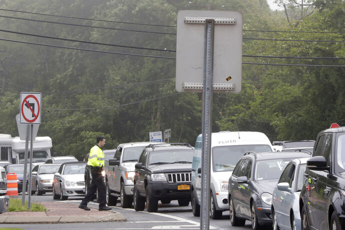 A police officer stands near traffic along County Road 39 near the site of the U.S. Open Golf Championship, Wednesday, June 13, 2018, in Southampton, N.Y. (AP Photo/Julio Cortez)