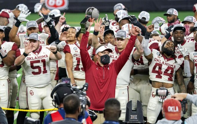 Oklahoma head coach Lincoln Riley hoists the Big 12 Conference championship trophy after defeating Iowa State 27-21 in an NCAA college football game, Saturday, Dec. 19, 2020, in Arlington, Texas. (AP Photo/Jeffrey McWhorter)