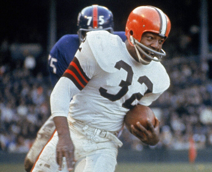FILE - In this Nov. 14, 1965, file photo, Cleveland Browns running back Jim Brown (32) carries the ball during an NFL football game against the New York Giants in Cleveland. Jim Brown. Period. Arguably the greatest player in NFL history was picked by the Browns with the No. 6 overall pick in 1957. Brown rushed for 12,312 yards in nine seasons, leading the league in eight seasons. The three-time MVP walked away from his career at its peak to pursue acting. (AP Photo/File)