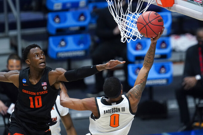 Oklahoma State guard Avery Anderson III (0) shoots on Oregon State forward Warith Alatishe (10) during the first half of a men's college basketball game in the second round of the NCAA tournament at Hinkle Fieldhouse in Indianapolis, Sunday, March 21, 2021. (AP Photo/Paul Sancya)
