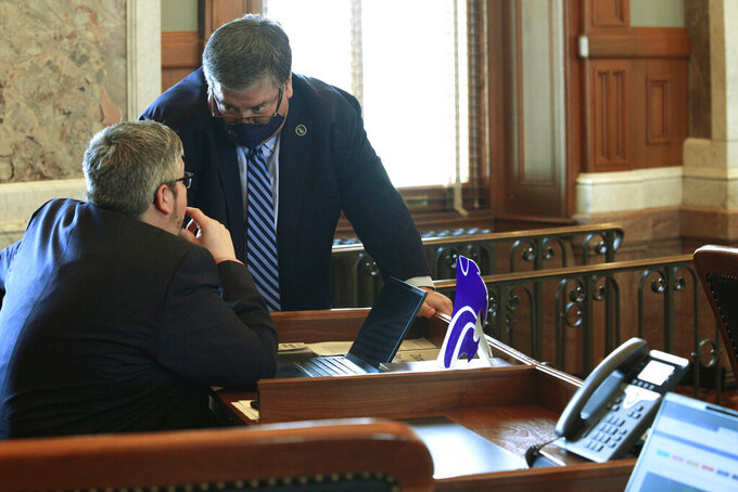 Kansas state Reps. Kyle Hoffman, left, R-Coldwater, and Ken Rahjes, R-Agra, confer during a House debate on a bill dealing with public schools and COVID-19, Monday, March 15, 2021, at the Statehouse in Topeka. The House has given first-round approval to the measure, which requires all school districts to offer all in-person classes to all students by March 26, 2021. (AP Photo/John Hanna)