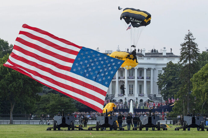 President Donald Trump and first lady Melania Trump watch as the U.S. Army Golden Knights Parachute Team descend during a