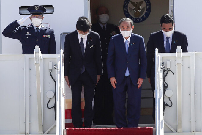 Japanese Prime Minister Yoshihide Suga boards his plane to depart at Andrews Air Force Base, Md., Saturday, April 17, 2021, after his visit to Washington. (AP Photo/Luis M. Alvarez)