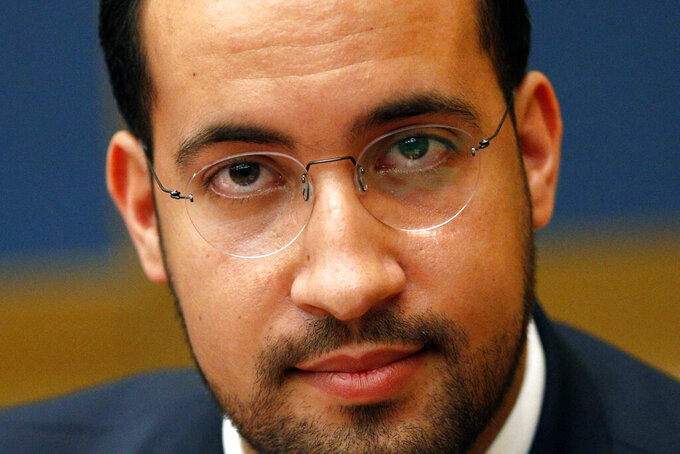 FILE - In this Sept.19, 2018 file photo, former President Macron's security aide Alexandre Benalla appears before the French Senate Laws Commission prior to his hearing, in Paris. Alexandre Benalla who triggered a political crisis when he was identified as having beaten up a protester during a 2018 May Day demonstration goes on trial Monday on a dozen charges, including voluntary violence, illegally wearing a police badge and carrying a weapon. (AP Photo/Thibault Camus, File)