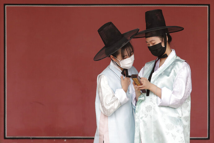 Women wearing traditional clothing and face masks to help protect against the spread of the new coronavirus look at a mobile phone at the Gyeongbok Palace, one of South Korea's landmarks, in Seoul, South Korea, Saturday, July 25, 2020. The country reported newly confirmed cases of COVID-19 over the past 24 hours, its first daily jump over 100 in nearly four months. (Photo/Ahn Young-joon)